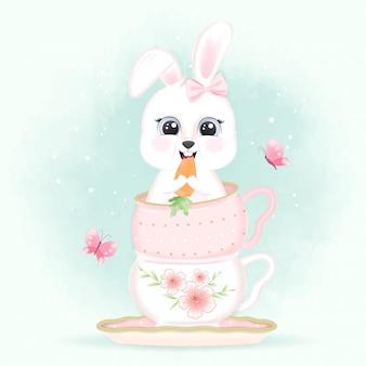Babykaninchen, das eine karotte in kaffeetasse und schmetterlingen isst
