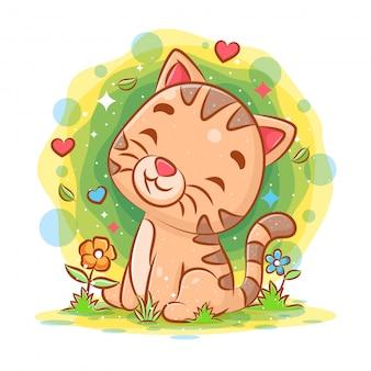 Babykatze, die im garten sitzt und lächelt