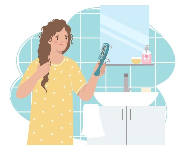 Badezimmer, frau hält einen kamm mit einer haarsträhne