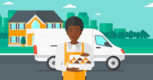 Bäcker, der kasten kuchen hält.