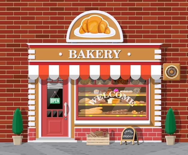 Bäckerei gebäude fassade mit schild. bäckerei, café, brot, konditorei und dessertladen. vitrinen mit verschiedenen brot- und kuchenprodukten.