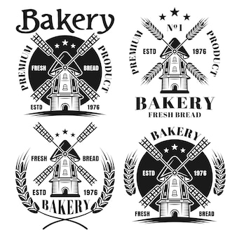 Bäckerei-set von vier vektorabzeichen, emblemen, etiketten oder logos mit windmühle im vintage-monochrom-stil isoliert auf weißem hintergrund
