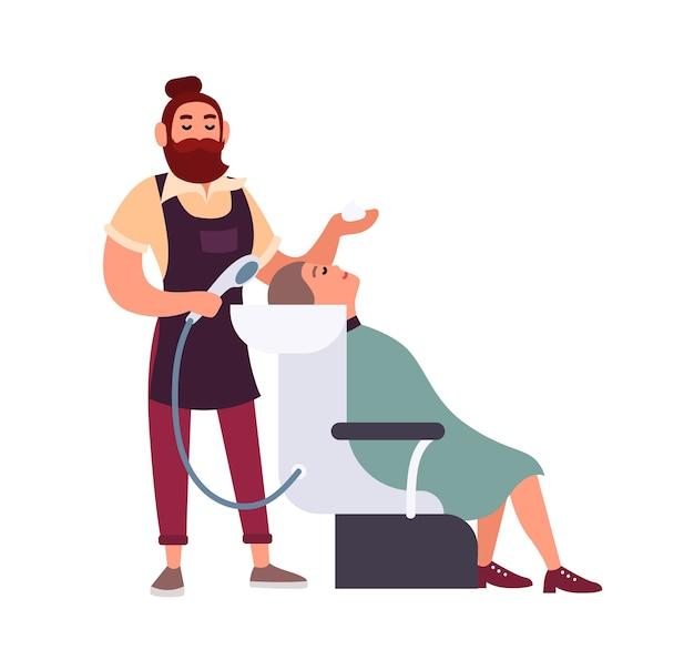 Bärtiger männlicher hipster-friseur oder stylist, der mit shampoo-haaren seiner fröhlichen kundin wäscht, die in stuhl isoliert sitzt
