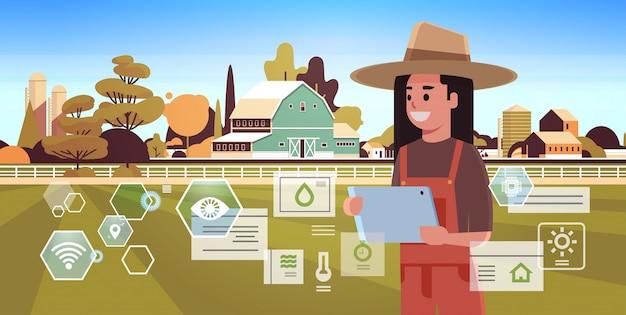 Bäuerin mit tablettenüberwachungsbedingung, die landwirtschaftliche produktorganisation der ernte des intelligenten landwirtschaftskonzepts farmbau-landschaftsporträt kontrolliert