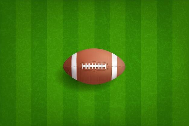 Ball des amerikanischen fußballs mit grünem gras.