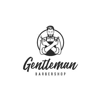 Barbershop-logo mit bärtigem mann, der schere und einen kamm hält