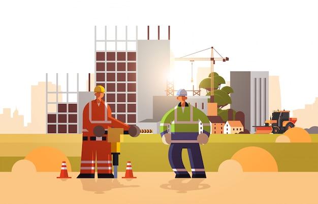 Bauherrenpaar bohren mit presslufthammer mit schutzhelm beschäftigte arbeiter, die zusammen industriearbeiter im einheitlichen baukonzept baustellenhintergrund horizontal flach in voller länge arbeiten Premium Vektoren