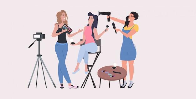 Beauty-blogger zeigen die neuesten trend-make-up-tutorials, die video-blog mit kamera auf stativ-blogging-konzept aufnehmen. frauen halten kosmetikprodukte in voller länge horizontal