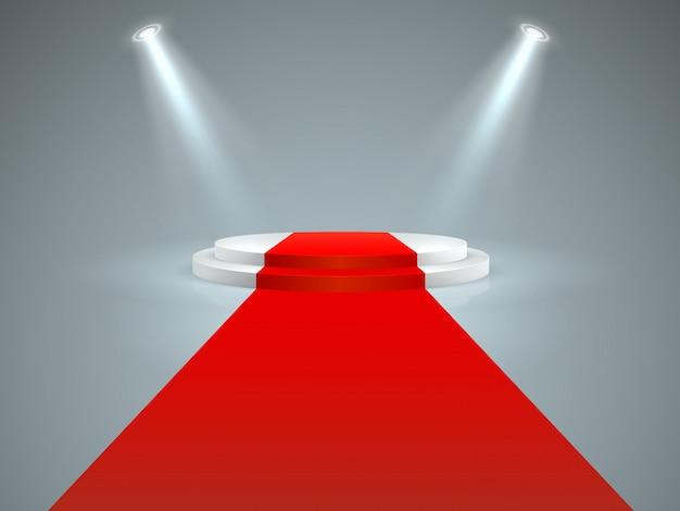 Beleuchtetes podium. bodenroter teppich zum weißen podium, scheinwerfer. hollywood-filmpremiere, vip-promi-lifestyle