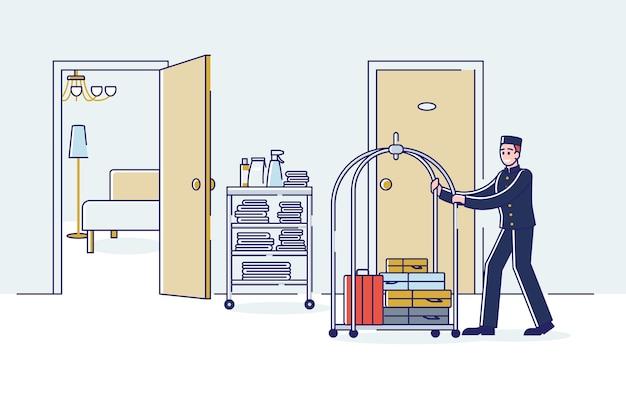 Bellboy, der gepäck auf wagen trägt. hotelportier in uniform mit besuchergepäck im hotelkorridor.