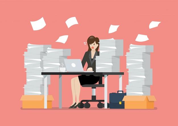 Beschäftigte überarbeitete frau, die bei tisch mit laptop und stapel von papieren im büro sitzt
