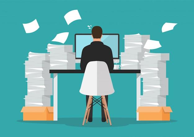 Beschäftigter geschäftsmann, der an computer mit stapel von papieren arbeitet