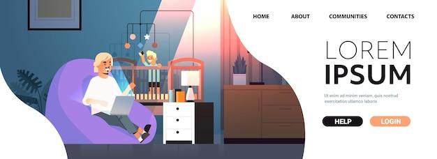 Beschäftigter vater freiberufler, der zu hause mit laptop arbeitet kleiner sohn spielt mit spielzeug in krippe freiberufliche vaterschaft konzept dunkle nacht wohnzimmer innenraum in voller länge horizontaler kopienraum