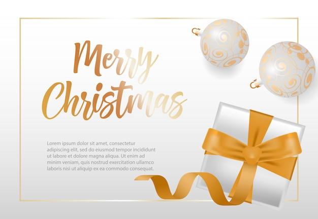Beschriftung der frohen weihnachten im rahmen mit kugeln und geschenkbox