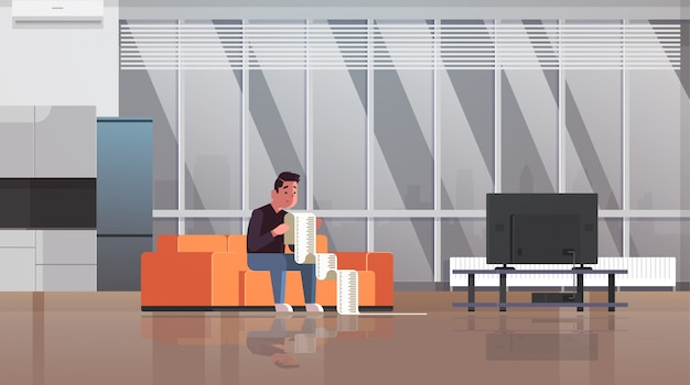 Betonter mann mit dem langen steuerdokumentschuldner, der durch zahlungsrechnungen finanzkrise-konkurs-konzeptkerl sitzt auf dem sofa entsetzt wird, sorgte sich um das zahlen viel des geldwohnzimmerinnenraums horizontal