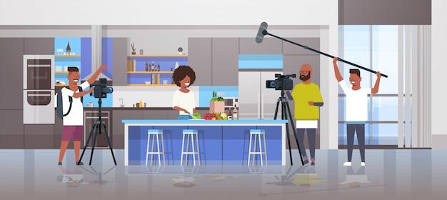 Betreiber, die videokamera verwenden, die nahrungsmittelbloggerin aufzeichnet, die leckere geschirrvideografen unter verwendung der professionellen ausrüstung kocht, die blog-konzeptkücheninnenraum horizontal kocht