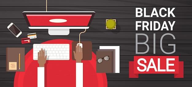 Black friday big sale unterzeichnen vorbei die hand, die auf dem computer-desktop über ansicht-feiertags-rabatt-fahnen-konzept schreibt