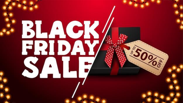 Black friday sale, rotes rabattbanner mit schwarzem geschenk mit preisschild mit angebot und girlandenrahmen, draufsicht.