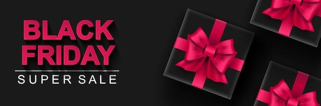 Black friday super sale banner schwarze geschenkbox mit rosa schleifen dunklem hintergrund großer saisonaler verkauf
