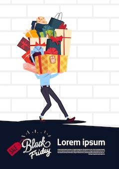 Black friday-verkaufs-plakat mit dem mann, der geschenkbox-stapel über weißem backsteinmauer-hintergrund hält