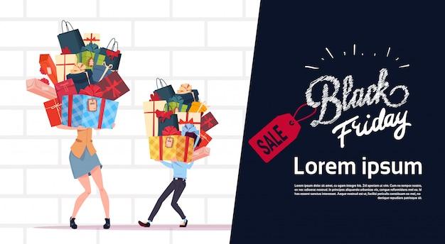Black friday-verkaufs-plakat mit den paaren, die geschenkboxen über weißem backsteinmauer-hintergrund halten