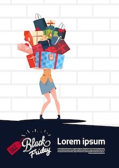 Black friday-verkaufs-plakat mit der frau, die geschenkbox-stapel über weißem backsteinmauer-hintergrund hält