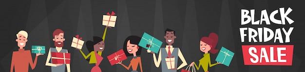 Black friday-verkaufstext über der gruppe von personen, die verschiedene geschenkbox-horizontale netz-fahne hält