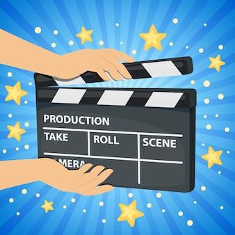 Blauer hintergrund mit händen, die filmklappe halten