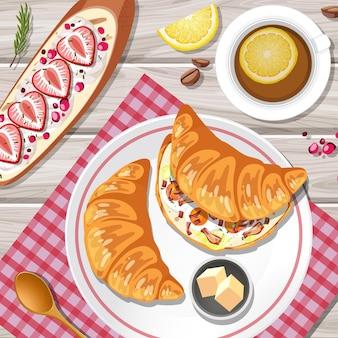 Blick von oben auf ein croissant mit einer teetasse auf dem tisch