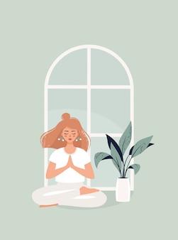 Blonde frau sitzt in lotussitz am fenster und topfpflanze