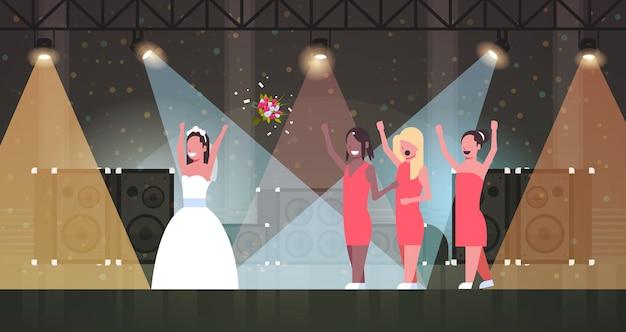 Braut im weißen kleid wirft blumenstrauß für brautjungfern, um mädchen zu fangen, die spaß auf bühnenlichteffekten disco studio hochzeitstag konzept in voller länge horizontal haben