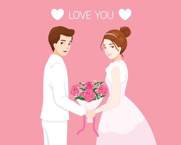 Braut und bräutigam in der hochzeitskleidung, die blumenstrauß zusammenhält, valentinstag