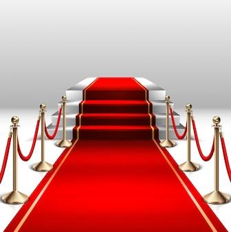 Bühne mit rotem teppich und goldbarriere.