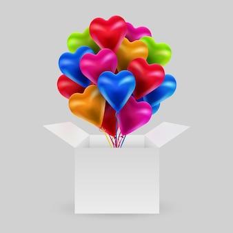 Bündel bunter luftballons in form eines herzens mit offener schachtel.