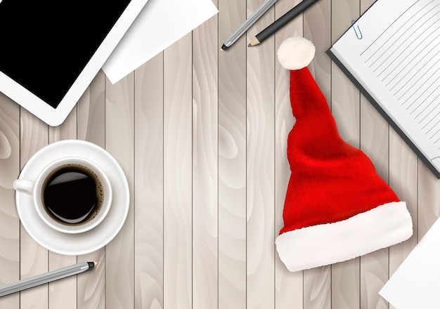 Bürohintergrund mit weihnachtsmütze, tablette und büromaterial