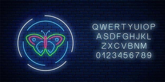 Bunte batterfly leuchtende leuchtreklame in runden rahmen mit alphabet auf dunklem backsteinmauerhintergrund. frühlingsfliegeremblem im kreis. nachtstraßenwerbungssymbol. vektor-illustration.