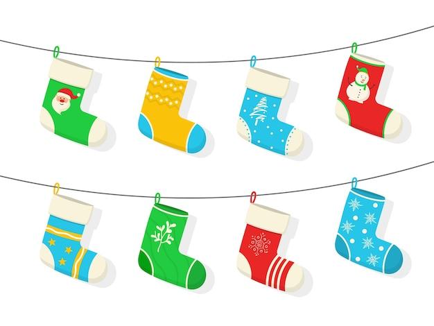 Bunte socken der weihnachts- und neujahrsfeiertage mit feiertagsmustern. verschiedene weihnachtssocken hängen an einem seil, das auf weißem hintergrund lokalisiert wird. wohnaccessoires, platz für gegenwart. illustration.