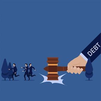 Business hand schlug hammer zu boden und team weglaufen metapher der schulden.