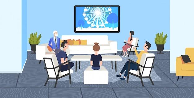 Businesspeoplesitting auf stühlen und sofa beobachten berühmte wahrzeichen tv-reiseshow konzept riesenrad silhouette im fernsehen modernen büro interieur in voller länge horizontal