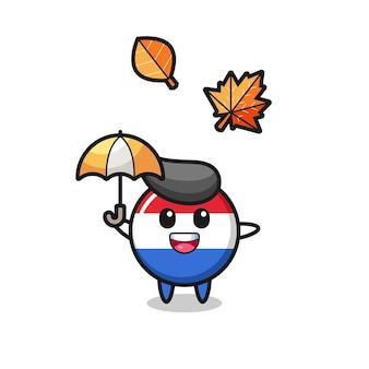 Cartoon des niedlichen niederländischen flaggenabzeichens, das im herbst einen regenschirm hält, niedliches design für t-shirt, aufkleber, logo-element