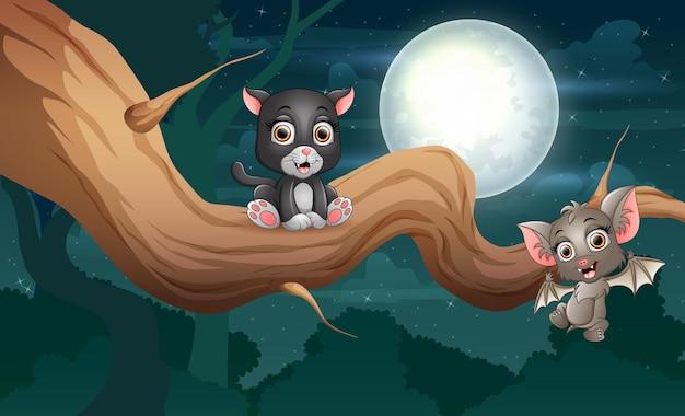 Cartoon eine fledermaus und eine schwarze katze auf einem baum in der nacht