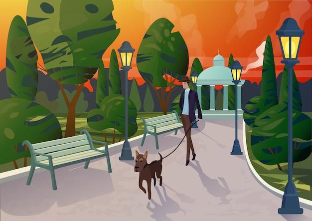 Charakter des eleganten mannes mit hund an der leine, der auf gehweg im stadtpark im sonnenuntergangslicht spaziert.