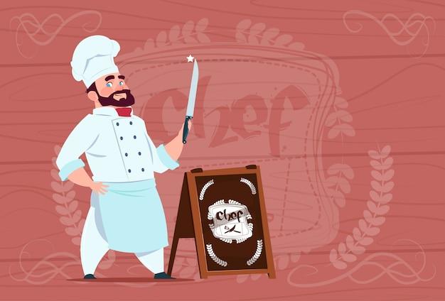 Chef-koch holding knife smiling-zeichentrickfilm-figur in der weißen restaurant-uniform über hölzernem strukturiertem hintergrund