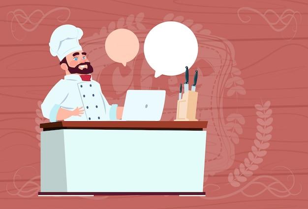 Chefkoch, der am laptop-computer-karikatur-restaurant-chef in der weißen uniform sitzt, sitzen am schreibtisch über hölzernem strukturiertem hintergrund
