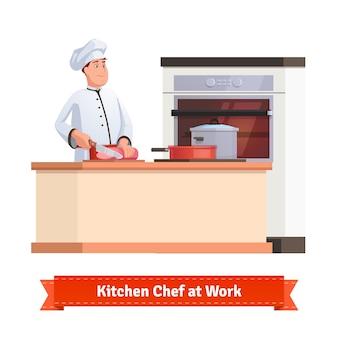 Chefkoch schneidet fleisch mit einem messer am tisch