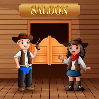Cowboy und cowgirl stehen vor dem saloon