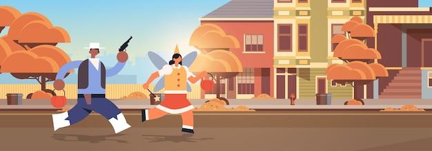 Cowboy und feenpaar, die mit kürbiskörben in stadttricks laufen und glückliches halloween-partyfeierkonzept stadtstraßengebäude außerhalb des stadtbildes behandeln