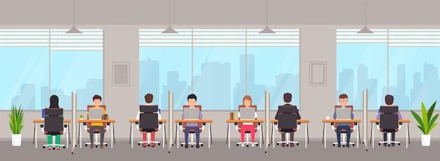 Coworking-space mit menschen. junge männer und frauen arbeiten an laptops hinter einem separaten arbeitsplatz mit trennwand im kreativbüro. gemeinsame arbeitsumgebung mit großen fenstern.