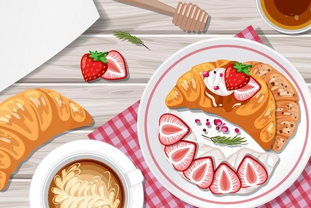 Croissant mit erdbeerbelag und einer tasse kaffee auf dem tischhintergrund