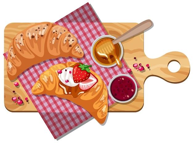 Croissant mit erdbeermarmelade und honig auf einem holztablett isoliert